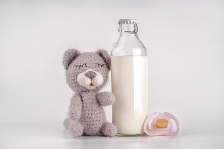 Bottle of milk with baby toy and pacifier white background Фото со стока