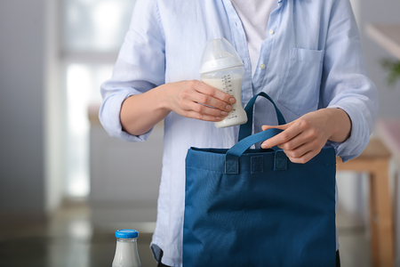 Woman putting feeding bottle of baby formula into bag