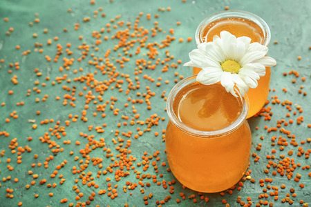 Jars of honey and flower on color background