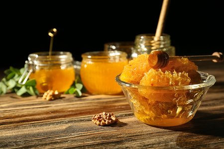 Bowl with sweet honeycomb and dipper on wooden table against dark background