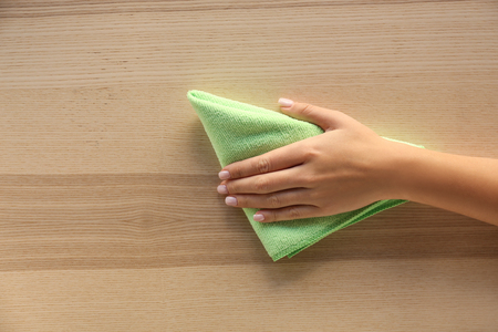 Woman cleaning wooden surface, top view
