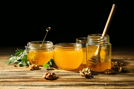 Jars with honey on wooden table against dark background