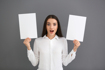 Emotional young woman with blank sheets of paper on grey background