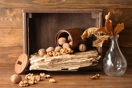 Composition with walnuts, old book and vase with dry leaves on wooden table Imagens