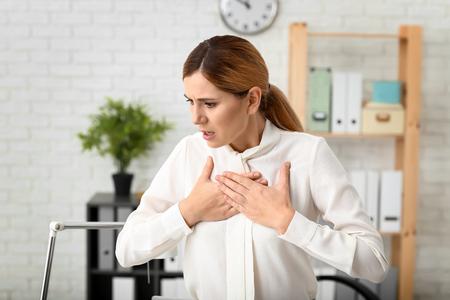 Vrouw met paniekaanval op de werkplek Stockfoto
