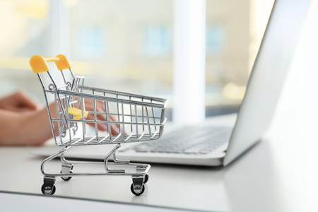 Small cart on table of woman using laptop. Internet shopping concept