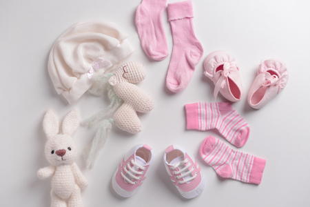 Baby clothes, shoes and toys on white background