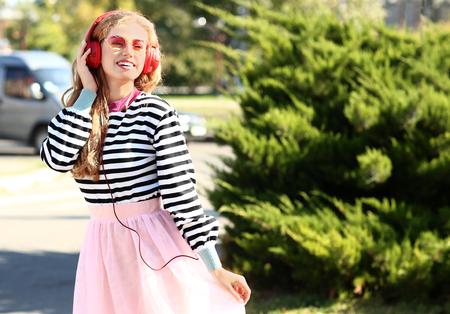 Beautiful young woman listening to music outdoors Standard-Bild