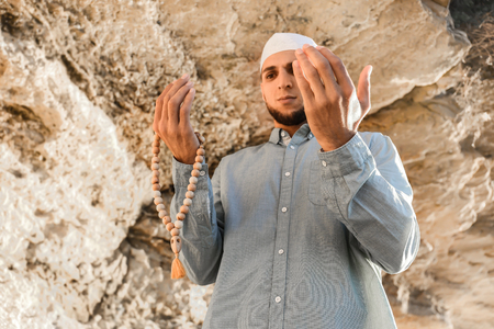 Young Muslim man praying outdoors Imagens