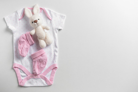 Cute baby clothes and toy on white background Stockfoto