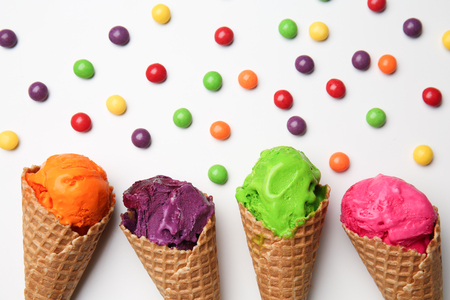 Waffle cones with delicious color ice cream and candies on white background Stockfoto