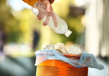 Woman throwing plastic bottle into garbage bin outdoors