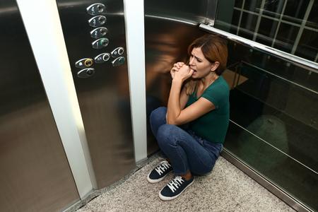 Woman having panic attack in elevator Stock Photo