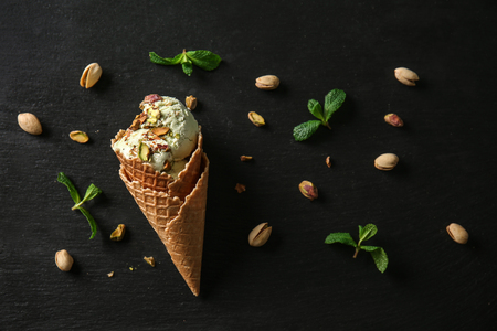 Waffle cone with delicious ice cream and pistachios on dark background Banco de Imagens