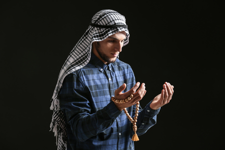 Young Muslim man with rosary beads praying on dark background Stock Photo