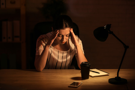 Woman suffering from headache while working at home late in evening