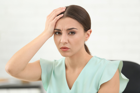 Woman suffering from headache indoors
