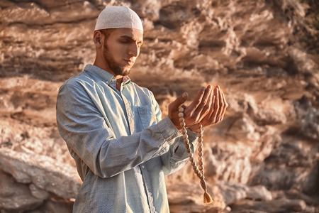 Young Muslim man praying outdoors 免版税图像