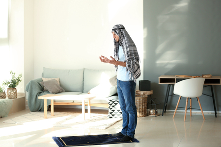 Young Muslim man praying at home