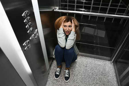 Woman having panic attack in elevator