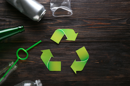 Different garbage with symbol of recycling on wooden background. Ecology concept Stock Photo