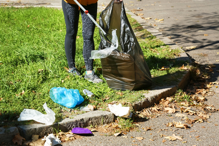 Woman gathering trash in park Stock Photo