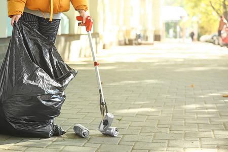Woman gathering trash on city street