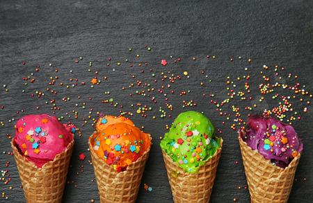 Waffle cones with delicious color ice cream and sprinkles on dark background Banco de Imagens