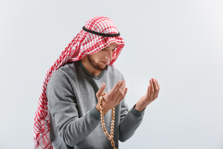 Young Muslim man praying on light background