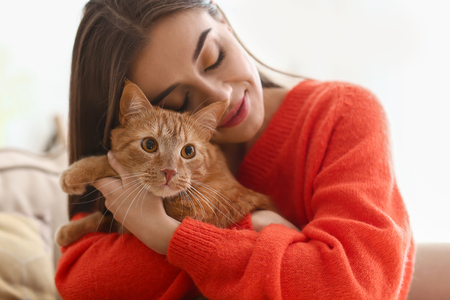 Woman with cute cat resting at home