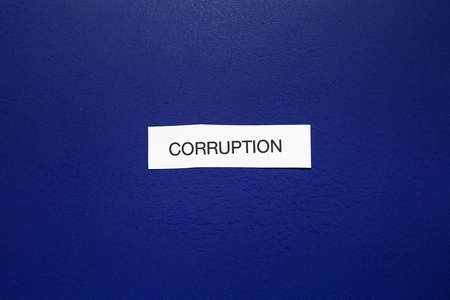 Piece of paper with word CORRUPTION on blue background 写真素材