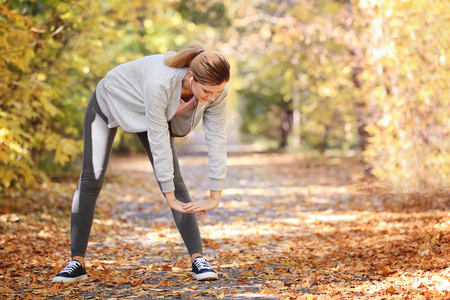 Sporty woman training in park on autumn day