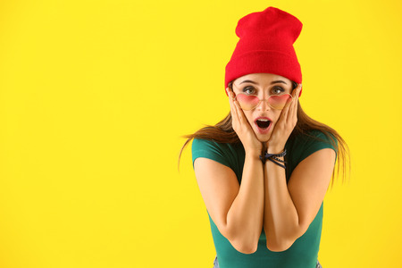 Emotional young woman after making mistake on color background