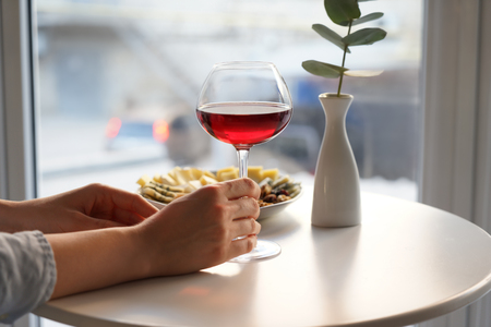Woman with glass of wine and snacks in cafe