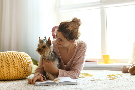 Woman with cute dog reading book at home on autumn day 스톡 콘텐츠