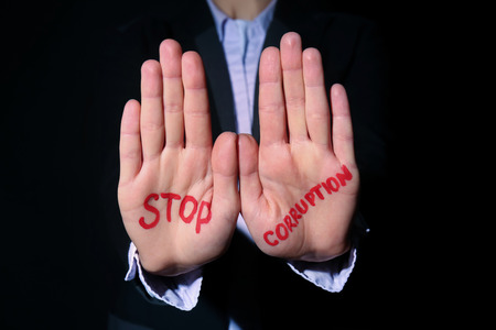 Woman with text STOP CORRUPTION written on her palms against black background, closeup