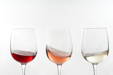 Glasses of different wine on white background