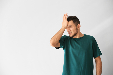 Emotional young man after making mistake on white background