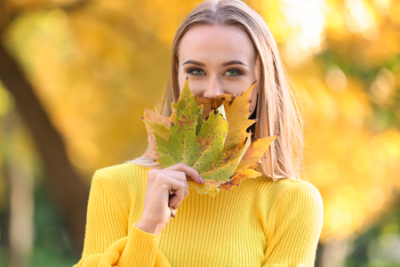 Beautiful young woman with autumn leaves in park