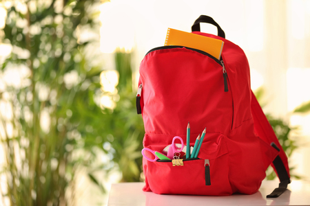 Backpack with school supplies on natural background Standard-Bild