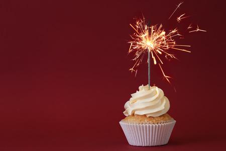 Leckerer Cupcake mit Wunderkerze auf farbigem Hintergrund