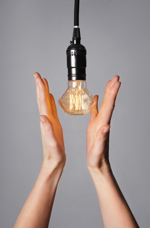 Female hands with glowing light bulb on grey background Archivio Fotografico