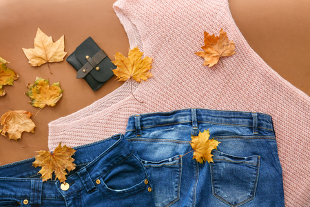 Stylish outfit with wallet and autumn leaves on color background, top view
