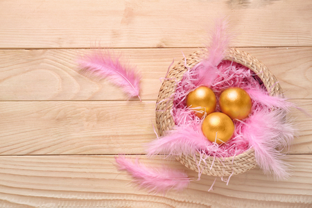 Wicker basket with Easter eggs on wooden table Stock Photo