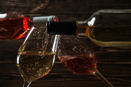 Pouring of wine from bottles into glasses on wooden background