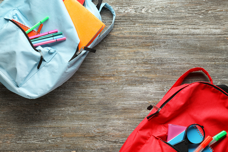 Color rucksacks with school stationery on wooden background
