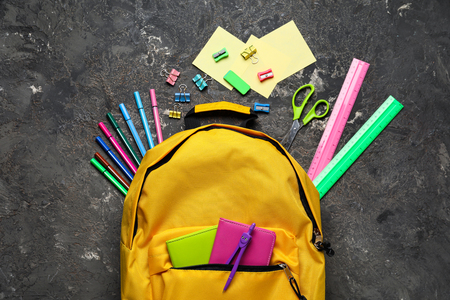 Composition with rucksack and school stationery on grunge background, top view