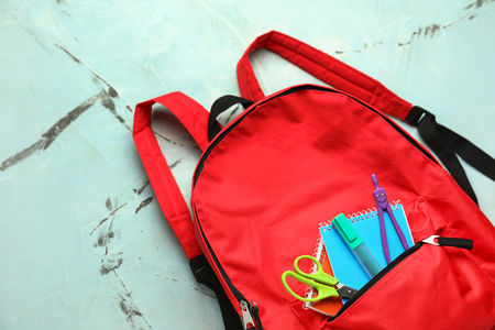 Cute rucksack with school stationery on color background