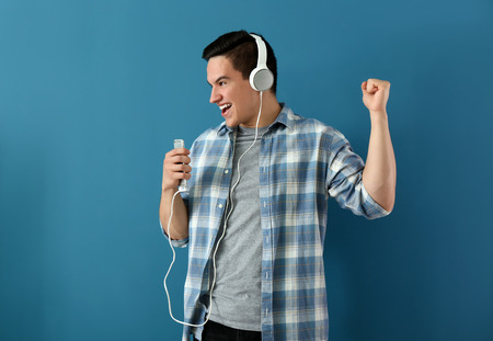 Emotional young man listening to music on color background