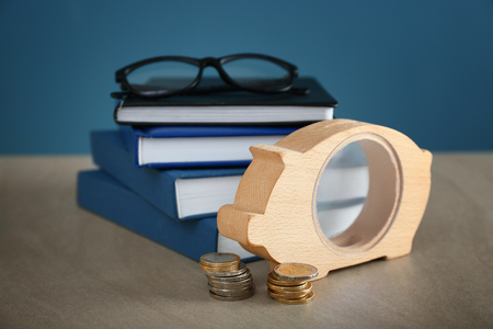 Piggy bank, glasses and stack of books on table. Concept of savings for education
